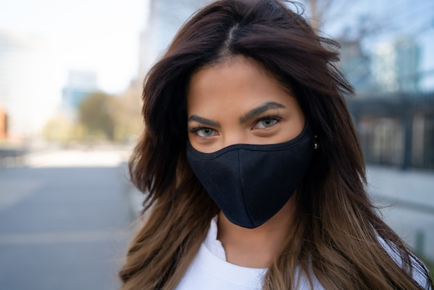 Крупный план молодой женщины в маске, стоя на открытом воздухе на улице. городская концепция. новая концепция нормального образа жизни.