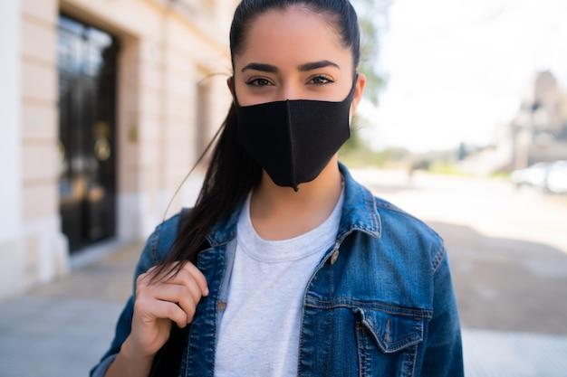 路上で屋外に立っている間フェイスマスクを身に着けている若い女性のクローズアップ