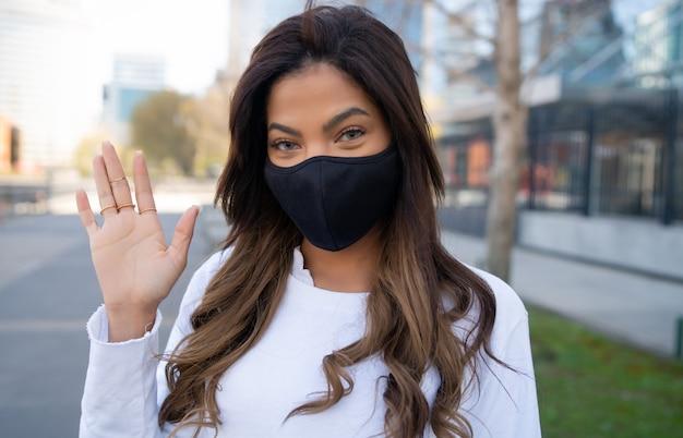 路上で屋外に立っている間、挨拶する保護マスクと手を振るを身に着けている若い女性のクローズアップ。アーバンコンセプト。