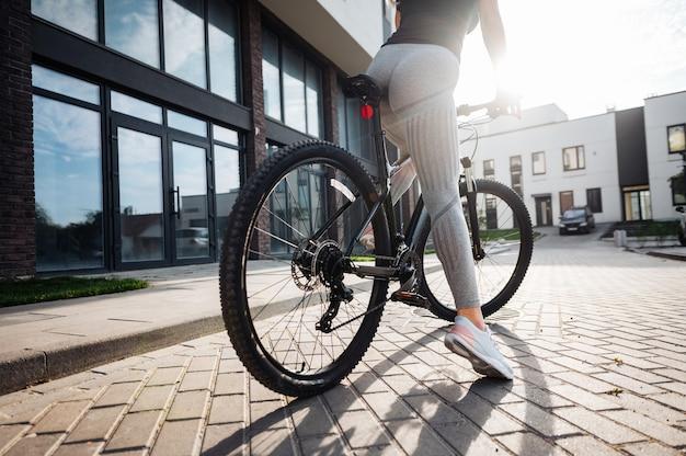 新鮮な空気で自転車に乗ってスポーツ服とスニーカーを身に着けている若い女性のクローズアップ。強い女性の脚に焦点を当てます。若い人のアクティブなライフスタイル。