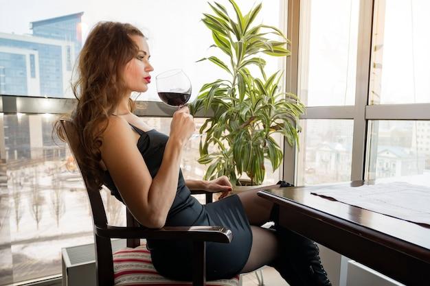 Закройте молодой женщины, которая ее рука с бокалом красного вина, глядя в окно. большой бокал красного вина в руке красивой девушки.