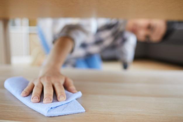방에있는 침대 아래에 걸레로 먼지를 닦아내는 젊은 여자의 근접