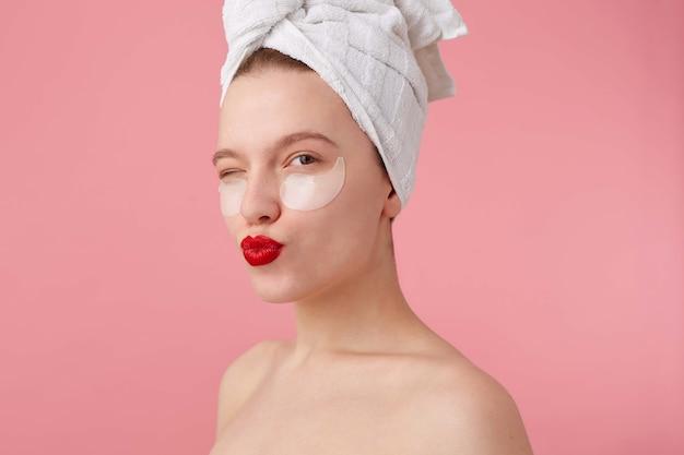 Крупным планом молодая женщина с полотенцем на голове после душа, с пятнами и красными губами, выглядит счастливой, посылает поцелуй и стоит.