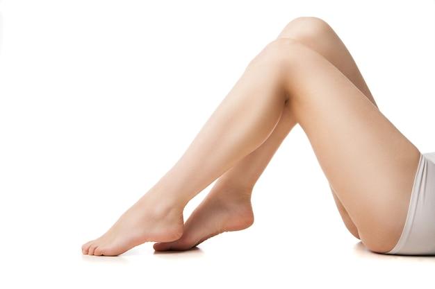 흰색 배경에 누워 아름다운 다리를 가진 젊은 여자의 근접