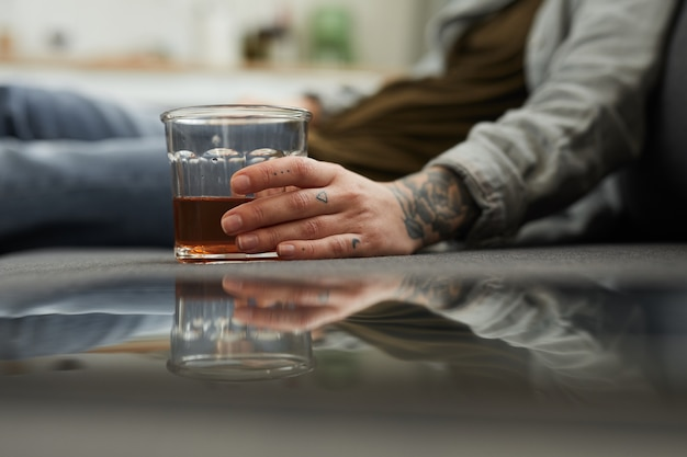 床に座って、家で飲むウイスキーのガラスと若い女性のクローズアップ