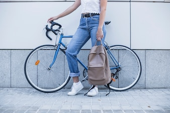 Close-up of young woman with her backpack standing near the bicycle