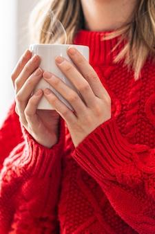 彼女の手でホットコーヒーのマグカップを保持している赤い綿のセーターを持つ若い女性のクローズアップ。冬の時間です。