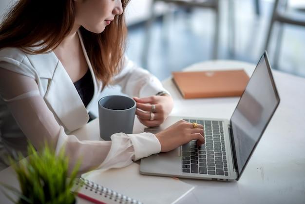 Крупным планом молодой женщины, работающей на портативном компьютере за столом в офисе