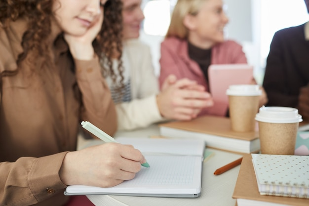 バックグラウンドで友人と大学図書館で勉強しながらノートに書いている若い女性のクローズアップ、