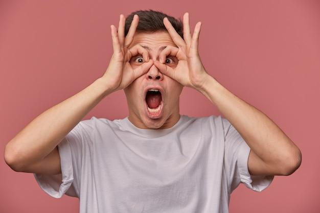 Крупным планом молодой удивленный парень в пустой футболке, выглядит хорошо, жестикулирует, делает маски пальцами, стоит на розовом с шокированным выражением лица.