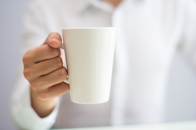 Close-up of office employee drinking coffee from mug