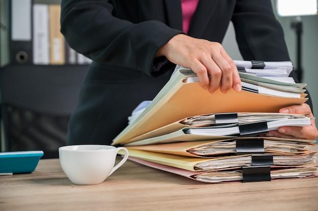 비즈니스 사무실의 비즈니스 데스크에서 문서 작업을 하는 사무실 직원을 닫습니다.