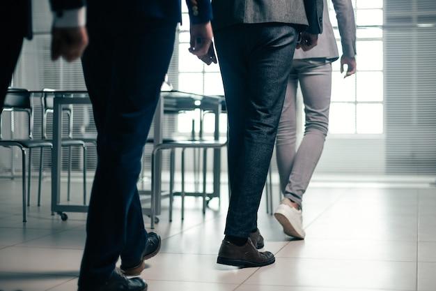 Закройте вверх. офисные сотрудники переходят на рабочее место. бизнес-концепция