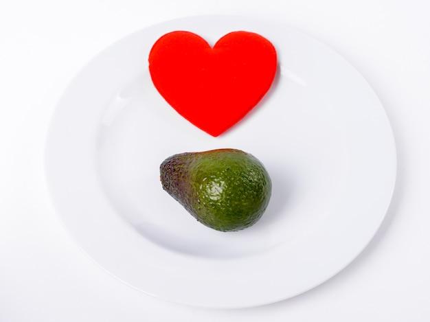 Красное сердце с авокадо на белой тарелке крупным планом