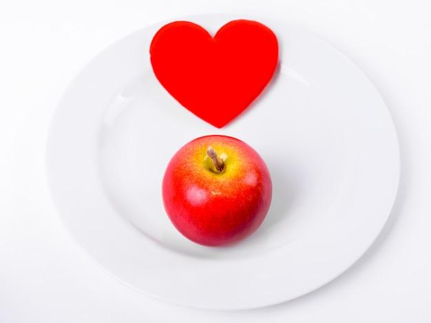 Красное сердце с красным яблоком на белой тарелке крупным планом