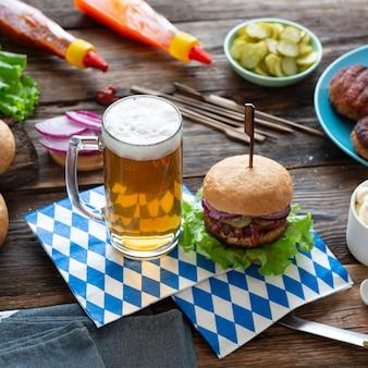 木製のテーブルにオクトーバーフェストビールとハンバーガーをクローズアップ