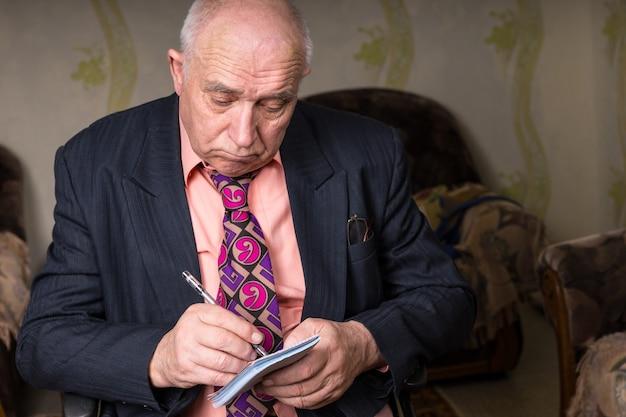 Крупным планом старый лысый бизнесмен в формальной одежде, что-то пишет в своих небольших заметках с грустным выражением лица