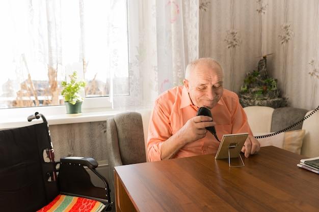작은 직사각형 거울이 있는 거실 테이블에서 전기 면도기로 수염을 청소하는 늙은 대머리 남자를 닫습니다.