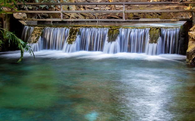 Close up of old concrete spillway in river at the tropical forest.