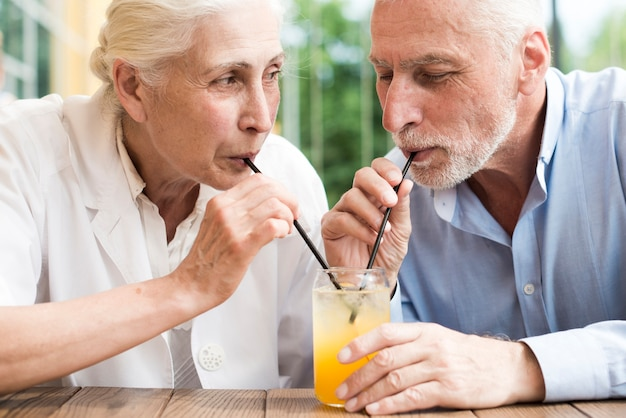 Close-up old couple drinking juice