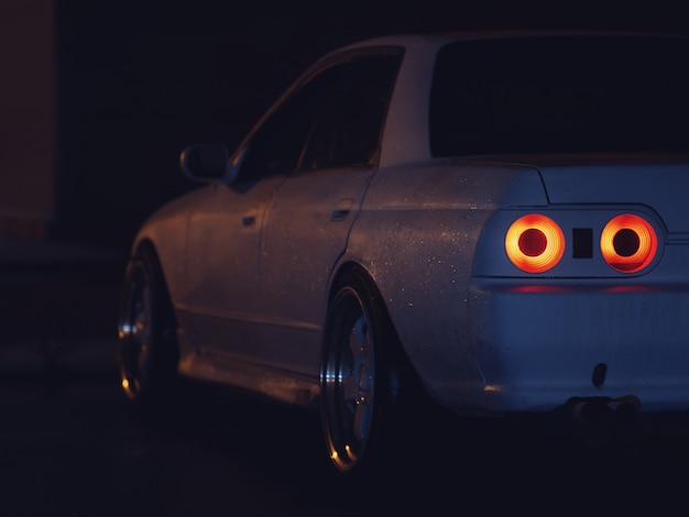 Close-up of an old drift sports car in the night parking lot . rear red lights