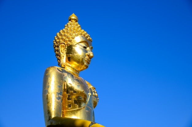 Close up old golden buddha statue against with blue sky