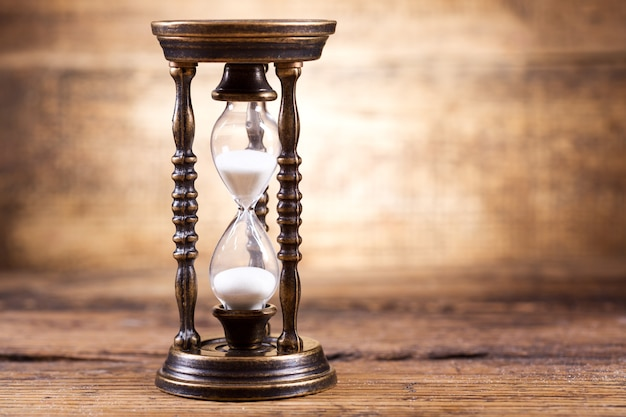 Close up of old hourglass on a wooden background