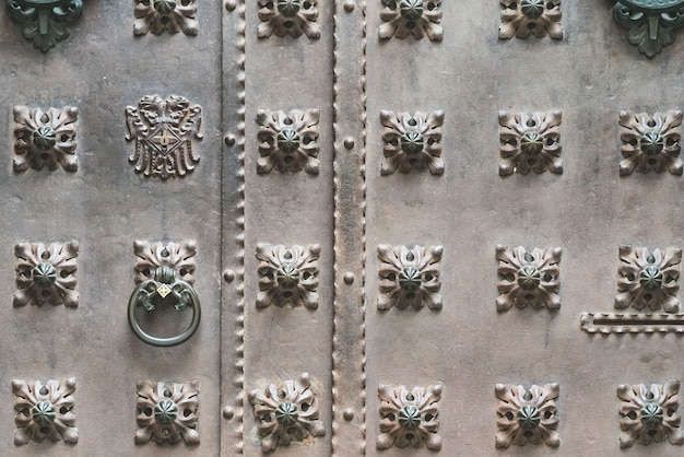 Close up of an old iron door with decorative studs