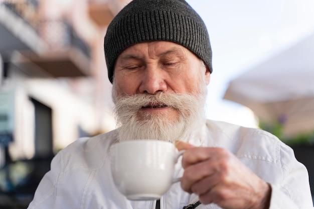 カップを保持している老人をクローズアップ