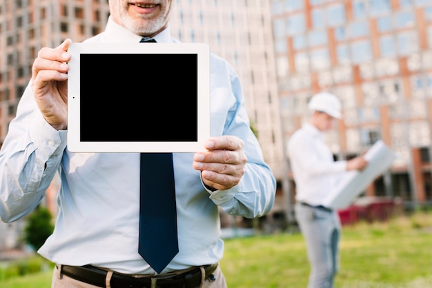 Close-up old man holding up a tablet