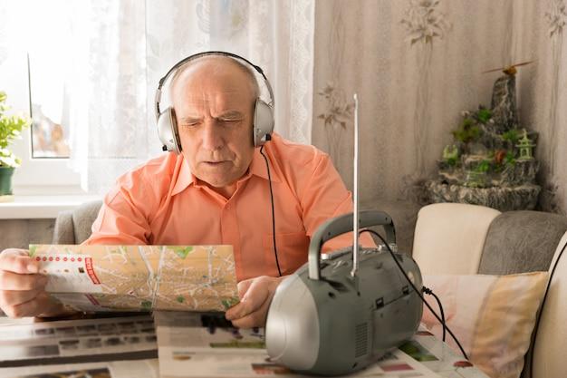 リビングルームエリアでタブロイド紙を読みながら、ヘッドセットでラジオから聞いている老人を閉じます。