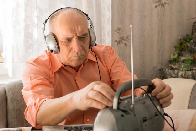リビングエリアに座っている間、ヘッドセットでラジオでニュース番組を聞いている老人を閉じます。