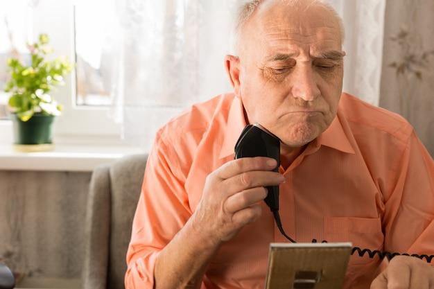 작은 거울 앞에서 진지하게 전기 면도기로 수염을 면도하는 노인을 닫습니다