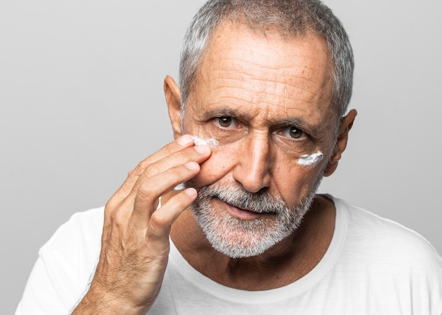 Close-up old man using face cream