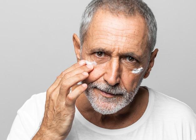 Uomo anziano del primo piano usando la crema per il viso