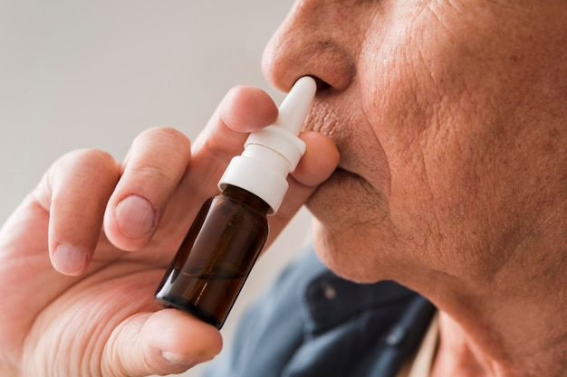 Close-up old man using nasal spray