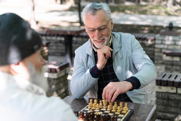 Close up old men playing chess
