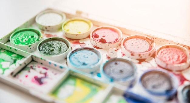 Close-up of a old messy watercolor palette