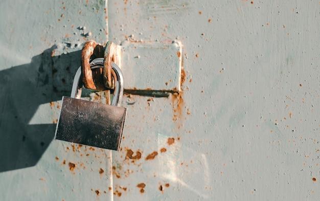 자물쇠를 가진 오래 된 금속 문을 닫습니다