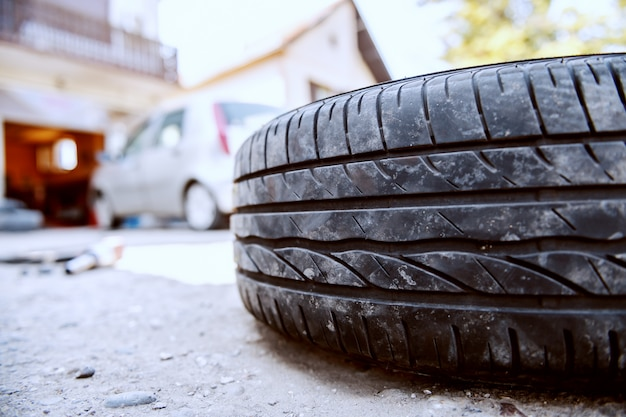 Close up of old tire on ground at auto mechanic workshop.