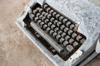 CLose up old typewriter. Part of rustic typewriter onconcrete floor.