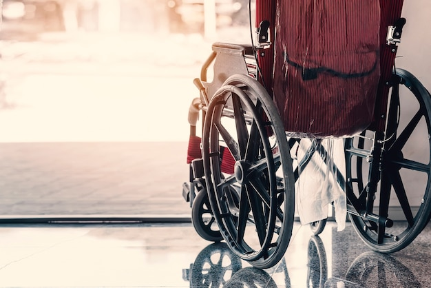 Close-up old wheelchair in front of the outpatient department of hospital with sunlight