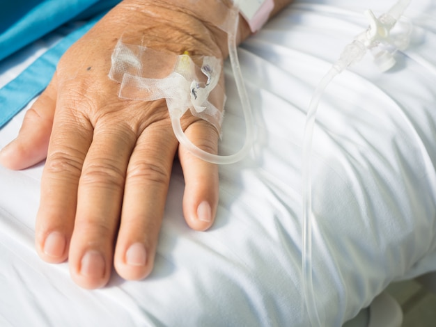 Close up old woman patient hand and iv set for fluid intravenous drop saline drip on white