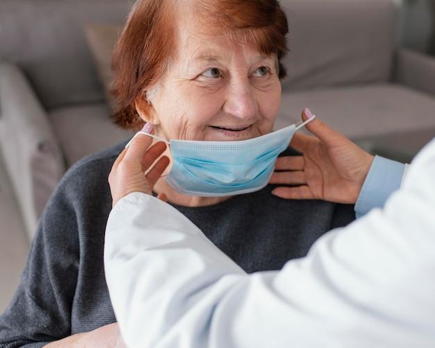 얼굴 마스크와 늙은 여자를 닫습니다