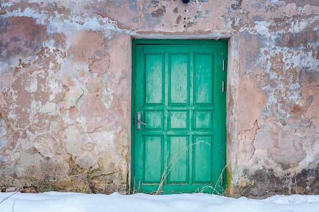 Close-up of old wooden door in winter time. menthol door in stone castle wall