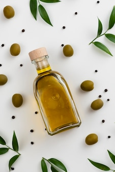 Close-up olive oil bottle with leaves next