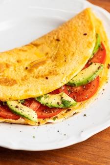 Close-up di frittata con pomodori e avocado sulla piastra