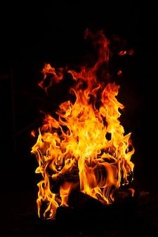 黒の背景に夜の焚き火の明るい炎のクローズアップ。暗い気分の写真。垂直フォーマット。