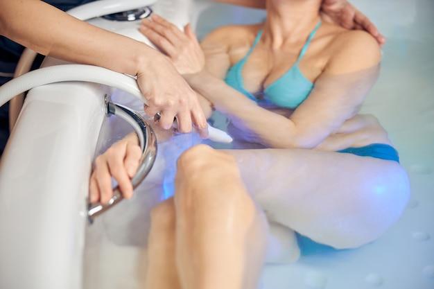 스파 욕조에서 수중 샤워 마사지를받는 백인 여자에 가까이