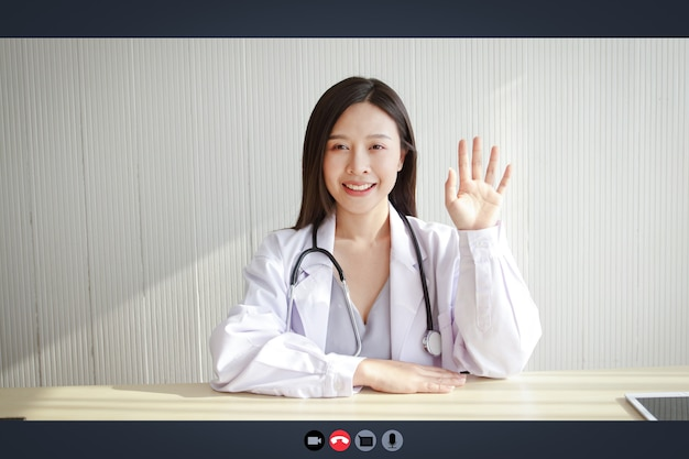コンピューター画面のクローズアップ、美しいアジアの女性医師がオンラインビデオ通話を介して患者を治療します